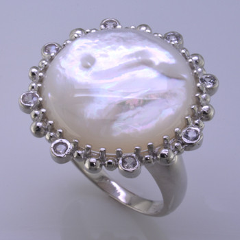 A Sterling Silver ring that says it's time for fun! A sizable 20mm Mother of Pearl surrounded by eight white Sapphires. You will be the talk of the party! Overall diameter is about 1 inch. Finger size 7 3/4.  Designed and created in Montreal, Canada.