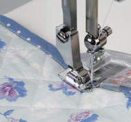 Use this foot for attaching tape to the edge of fabrics. Adjust the needle drop position with the thumb screw. Guide the fabric with the left hand and tape with the right hand.