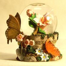 "MINITURE SNOW GLOBE WITH BUTTERFLYS & FLOWER  MEASURES 2 1/2"" X 2"" X 3 1/8"""