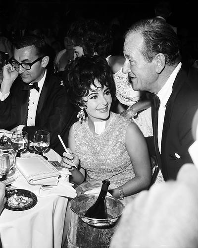 This is an image of 194817 Elizabeth Taylor and John Wayne Photograph & Poster