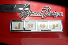Jeep tailgate emblem, reproduction tailgate emblem.  White background with gold letters.. Metal casting, chrome plated, raised letters,  polished, painted to original colors.  Comes with mounting hardware.  Number 16 in the diagram        Licensed Mopar Reproduction emblem.