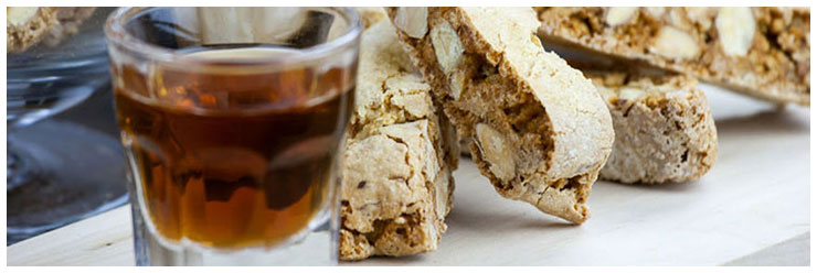 Vin Santo sweet wine served with Cantucci, typical Tuscan almond biscuits, on a table.