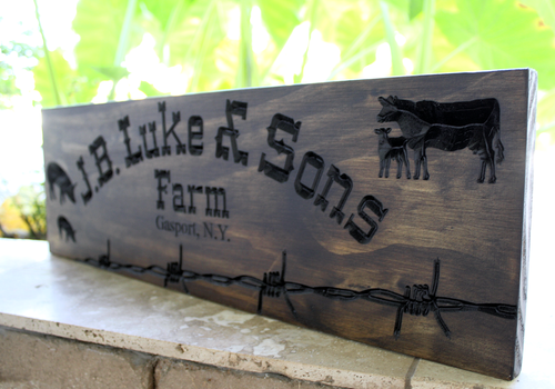 farm sign with pigs and cows and barb wire