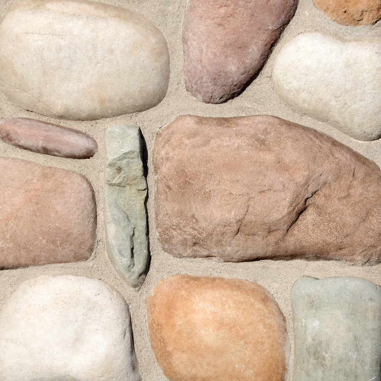 Picture of a River Rock stone siding in the Mountain color palette by Superior Stone (made in the Pacific Northwest).  Shown here with dark mortar bed.