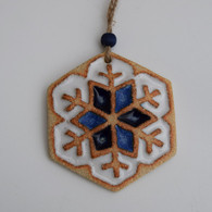 Snowflake decoration made from stoneware clay and coloured glazes. Hessian string and bead added to hang. Supplied on a product card.