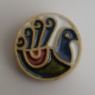 Peacock Brooch made from a white stoneware clay and coloured glazes. Piece comes displayed on a product card.