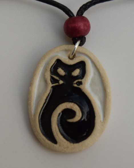 Cat pendant made from a white stoneware clay and coloured glazes. Comes on a black waxed cord choker with lobster clasp and extension chain. Piece comes displayed on a product card.