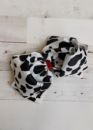 "A large double looped grosgrain ribbon hair bow in a cute black and white cow print.  Attaches with a large 3"" alligator clip with ""teeth"" for a secure hold.  The bow measures approximately 6.5"" long and 5"" wide."