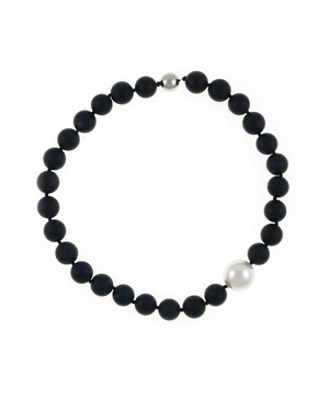 London Eye Pearl and Onyx Necklace: Single strand black untumbled onyx beads 14mm, featuring an offset single shell pearl 20mm, on individually hand-knotted black silk, with rare earth magnetic mixed metal clasp