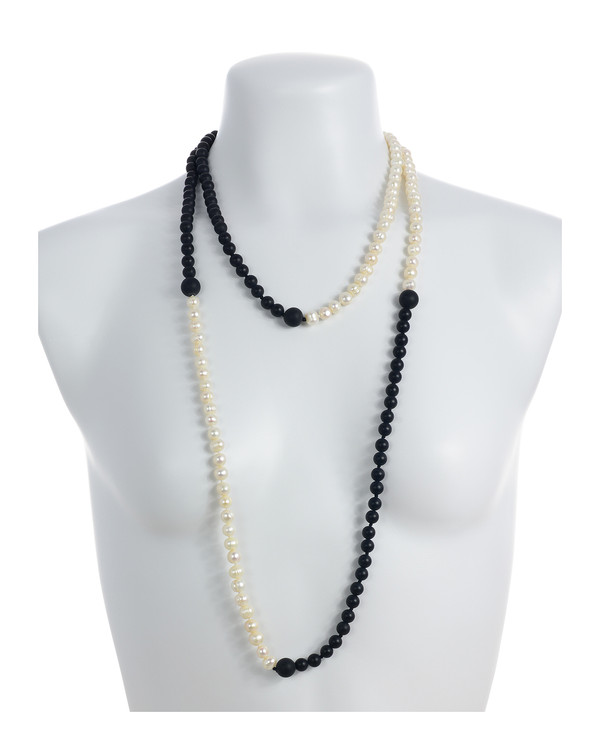 Copacabana Promenade I - Pearl Necklace Accented with Onyx On model: Single strand white freshwater pearls 7.5mm, transitioning to untumbled onyx beads 8mm, punctuated with 14mm untumbled onyx beads, on individually hand knotted natural silk