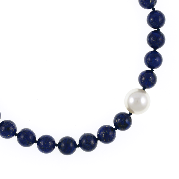 Côte d'Azur - Lapis and Pearl Necklace Zoom showing offset shell pearl: Single strand lapis beads 14mm flecked with pyrite, with offset shell pearl 20mm, on individually hand knotted black silk, featuring rare earth mixed metal magnetic clasp