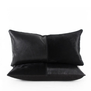 As Shown: Duality Black Pillow Size: 9 x 18 inches Material: Leather, Cowhide Color: Black Description: You'll get the best of both worlds when sleek leather and rich cowhide unite in deepest black. Artisans seam the two materials then back with black linen or leather. Fitted with a feather and down inner, your pillow will be individually hand made for you. The ideal pillow for perfect understated cool.