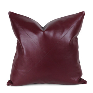 As Shown: Burgundy Leather Pillow Size: 16 x 16 inches Material: Leather  Color: Burgundy  Description: This glossy supple piece, available in three styles for your customization, is your go-to classic in soft durable deep oxblood red napa leather. Throw it anywhere for timeless sophistication. Artisans finish the full-grain sheepskin hide front per your specifications, then back in matching leather. Fitted with a feather and down inner and hidden zipper, your pillow will be individually created for you.