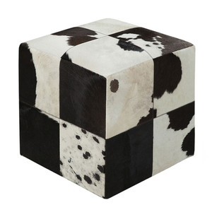 As Shown: Farmhouse Hide Pouf  Size: 18 x 18 x 18 H inches Material: Hair-On Cowhide  Description: A patchwork of black and white spotted hair-on cowhide brings organic impact to a modern piece. By hand artisans seam a patchwork of hair-on cowhide over an upholstered body. Each pouf is individual to you, please allow for variation in color and markings. A striking dose of nature as at-home in minimal industrial spaces as it is contrasting traditional patterned brights.