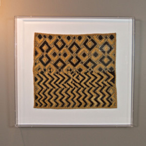 As Shown: Authentic African Cloth Weaving Size: 30.5 x 28.5 H inches Material: Kuba Textile Frame: Acrylic  Description: A striking juxtaposition of textured tradition and clear modernity creates a unique art piece. A handcrafted African textile is mounted on white linen and floated in an acrylic shadowbox. Each piece is unique, please contact us if you would like to see the actual cloth that you will be receiving. As part of a vignette over an entry table; two paired for creative harmony.