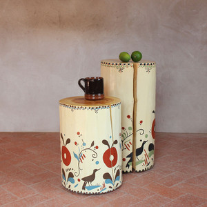 As Shown: Pajarito Hand Painted Side Table Size: 12 dia x 16 H inches Color: Bone and Ivory Topcoat: Sealed Topcoat  Description: Be charmed by naive style inspired by the motifs on traditional Spanish Colonial pottery. Each one-of-a-kind piece is hand painted by New Mexico artist J. Myers. A solid pine log is sanded smooth and its sides are painted. A natural wood grain top – protected by a clear finish – and cracks that are inherent to the wood impart sophistication and a rough authenticity. Its winsome artistry is a disarming presence in your cozy abode.