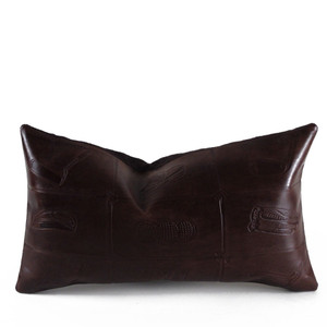 As Shown: Hole In One Pillow Size: 10 x 18 inches Material: Leather Color: Chocolate Brown  Description: With a cool vintage sportif vibe, embossed clubs form quadrants, each containing a golf motif. By hand, artisans emboss the leather face with a pattern of iconic golf images, including a putter, tees, balls and gloves. Backed with linen or leather and fitted with a feather and down inner, your pillow will be individually created for you. In a back-supporting lumbar size, it makes the ideal gift for your favorite golfer after a day on the links.