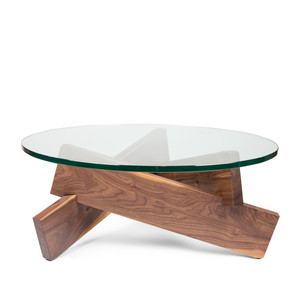 As Shown: Burbank Coffee Table Size: 36 diameter x 15 H inches Material: Solid Walnut with Glass Top  Description: Luxuriously grained solid walnut support a round tempered glass top table, reminiscent of a campfire. If a campfire were created by a modernist to evoke a feeling of warmth, spaciousness and homey hospitality without all that pesky smoke and ash.