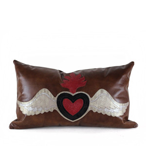As Shown: Sagrado Corazón Pillow Size: 12 x 20 inches Material: Leather Color: Tobacco Brown  Description: Celebrate the classic western iconography of the Sacred Heart in rich layers of embossed, appliqué leather.  By hand, artisans emboss, cut and outline each piece with a topstitch, then back with matching linen or leather.  Fitted with a feather and down inner, your pillow will be individually created for you. It's a bold, singularly beautiful piece for your distinctive home.