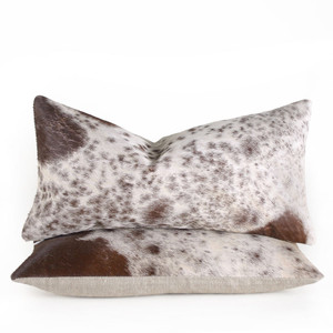 As Shown: Spot-on Hide Pillow Size: 9 x 18 inches Material: Cowhide Color: Brown Spotted Description: Add pastoral elegance to your interior with these lovely brown spotted cowhide pillows. By hand, artisans back hair-on cowhide with linen or leather and fit with a feather and down inner. Each pillow is unique to you; please allow for variation in color and pattern. Perfect from sectional to chesterfield, we love upping the impact of their natural variations by herding a few together.