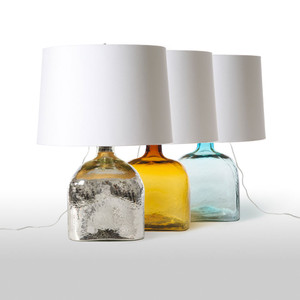 As Shown: Santa Monica Table Lamp Size: 19 diameter x 26 H inches Material: Glass  Shade: Silk Color: Silver, Amber or Aqua  Description: The seaside fun and breezes of Santa Monica shine through these square glass table lamps. Their bottled-summer shape is available in shimmering silver, sunset amber, and ocean aqua - each topped by a sail-white shade. Who says dreaming only happens in California?