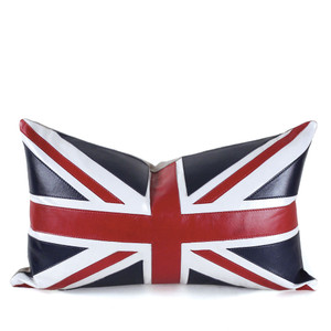 As Shown: Union Jack Pillow Size: 12 x 20 inches Material: Leather Color: Blue, Red and White  Description: London calling all Anglophiles: double-decker bus red, bobby uniform blue, and clotted cream white unite as the classic symmetry of the British flag gets leathered up and made even cooler with a natural linen or matching blue leather back. By hand, artisans cut and attach the leather strips with a topstitch outline. Fitted with a feather and down inner, your pillow will be individually created for you. Toss it in for a bit of cheek from the motherland. Long live the Queen!