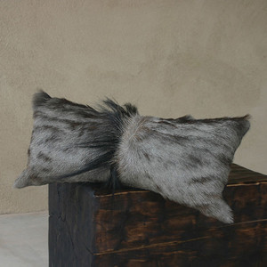 As shown: Genuine Wildebeest Hide Pillow Dimensions: 9 x 17 inches Materials: Hair-on hide  Description: Bask in wild luxury with a pillow created from a Genuine African Wildebeest hide. This deep dark stunner effortlessly juxtaposes with your timeless style. Handmade-to-order, artisans craft these premium designer-quality cushions from natural wildebeest hides. Backed in black fabric with a feather and down inner, each pillow is individual to you; please allow for variation in color and markings. Some have a fluffy spine down the center, on others it is less visible.