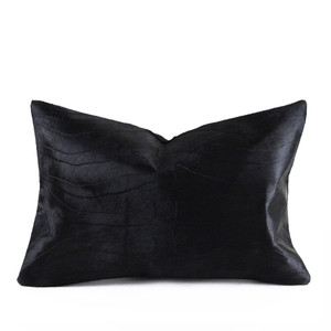 As Shown: Savanna Zebra Embossed Pillow Size: 12 x 20 inches Material: Cowhide  Color: Black Description: A zebra of a different color in three embossed solid shades. By hand, artisans emboss a zebra print onto hair-on cowhide then back with linen or leather. Fitted with a feather and down inner, your pillow will be individually created for you. A subtle way to inject a striking print no matter where you call home.