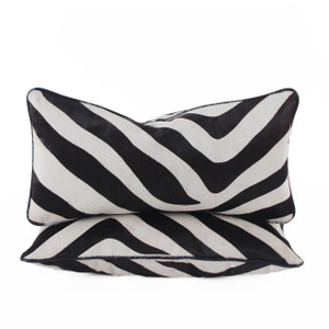 As Shown: Zambezi Zebra Hide Pillow Size: 9 x 18 inches Material: Cowhide  Description: Striking stripes make for high-impact in an amazing replica of a genuine Zebra hide backed in leather. Using a dark brown dye stain, artisans hand-paint the pattern onto off-white hair-on cowhide then back with black linen or leather.  Finished with black leather piping and fitted with a feather and down inner, your pillow will be individually created for you. Its luxe contrast lends head-turning chic from penthouse to lodge.