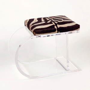 As Shown: Clifton Road Bench Size: 25 x 18 x 20 H inches (each is unique based on the size of the actual hide) Material: Authentic Zebra Hide on Acrylic Base  Description:  A show-stopper for your interior, a genuine zebra hide hide tops a curvaceous acrylic bench for an impactful juxtaposition of dramatic lines and distinctive upholstery. By hand artisans attach a genuine zebra hide seat. Handmade-to-order, dimensions will vary slightly due to natural variations in hides.