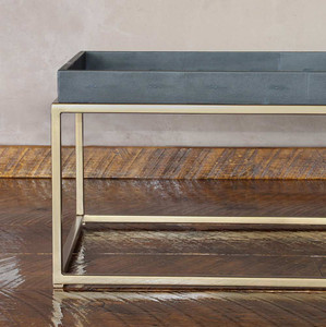 As Shown: Brentwood Leather and Brass Cocktail Table Size: 22 x 60 x 17 H inches Material: Steel with Brass Finish, Leather  Description: The texture of dark grey faux shagreen leather partners with a smooth antique brass finish in an airy, masculine piece.