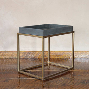 As Shown: Brentwood Leather and Brass Cocktail Table Size: 16 x 22 x 21 H inches Material: Steel with Brass Finish, Leather  Description: The richly elegant contemporary combo of dark grey faux shagreen leather and smooth antique brass creates a classic end table. By hand our artisans in India emboss leather for a fine pebbled finish and stretch over a wooden frame, the iron base is finished in brass.