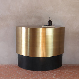 As Shown: Jules Deco Brass Console Size: 36 x 12 x 30 H inches Material: Brass, Leather  Description: A swath of antiqued brass curves above black leather in a rich contrast of light and dark, shine and matte, to form a new iconic classic. Equally at home in minimal or traditional spaces, this sophisticated brass and leather console is a Pfeifer Studio exclusive hand-crafted by our artisans.
