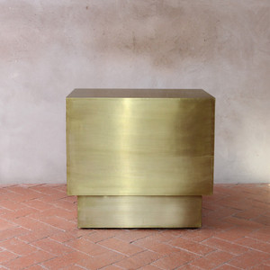 As Shown: Latón Brass End Table Size: 24 x 16 x 22.5 H inches Material: Brass  Description: An antique finish radiates glowing warmth over a brass end table with clean lines and streamlined style. Flashing with understated brilliance, it is equally at home in minimal or traditional spaces. This architectural piece is a Pfeifer Studio exclusive hand-crafted by our artisans.