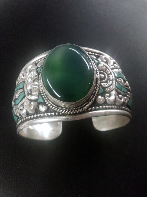 Gorgeous white metal Tibetan Bangle with Green Onyx stone placed in the center with torquoise inserts through bangle. Approximately 3-4cm wide.