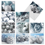 Silver ornaments with glitter, patterns, mirrors and snowflakes rest on a backdrop of freshly fallen snow.