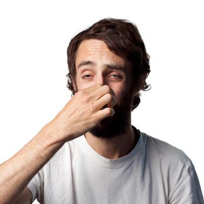 man pinching his nose sensing a bad smell