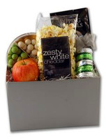 Welcome themed gift basket arrangement filled with fruit, chocolates, sweet and salty snacks, and drink