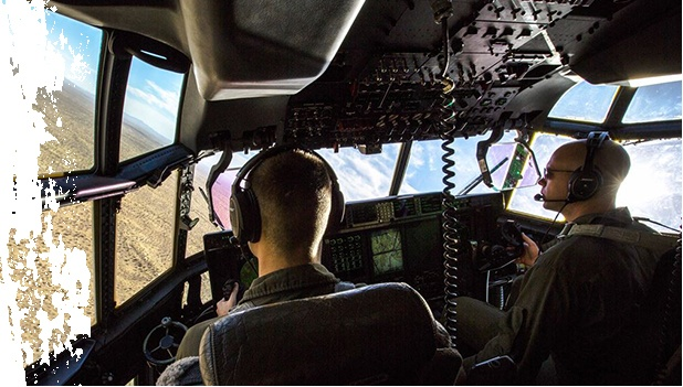 Interior Image of Two Military Men Flying A Helicopter Over A Desert