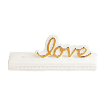 """This new Nora Fleming """"Love"""" sign has so many possibilities! It will make an adorable accessory for all over your home!  Imagine one piece that changes for every holiday, event or season. All you have to do is remove one mini, add another and presto a whole new look!     Dimensions: 10"""" x 3"""" X 4""""      Compatible with Nora Fleming mini ornaments (sold separately)     How it works:  Step 1: Dab the hole of your sign with water Step 2: Insert the decorative mini of your choice Step 3: Pull the stem down from the bottom so that the mini sits flush on the rim"""