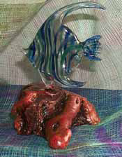 Glass fish sculpture on wood base