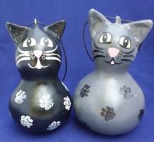 The black cat has white paw prints. The gray cat has black paw prints.