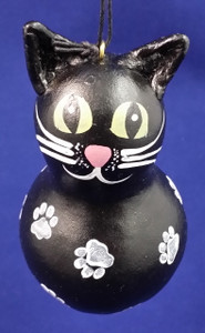 The black cat has white paw prints all over!