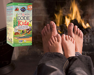 Two pairs of feet, one larger like a father's, and one smaller like a child's, sitting right on top of the first pair, in front of a fireplace fire, with a box of Garden of Life Vitamin Code Kids Whole Food Multivitamins for Children.