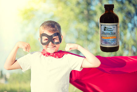 Boy with a mask and cape like a super hero, flexing his arm muscles; on the right is shown a bottle of Green Pastures Blue Ice Fermented Cod Liver Oil.