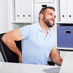 man working at a Desk with back pain