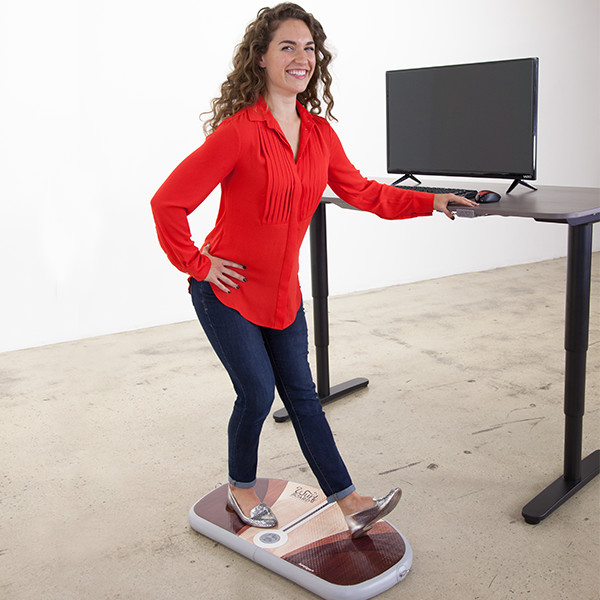 woman working at a stand up desk with a wurf board doing exercises