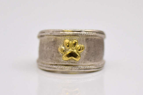 I hand crafted the paw print ring in sterling silver with an 18 k yellow gold paw.  The ring is 12 mm. tapering to 5 mm. and is a size 6.  The ring can be sized upon request.  The ring weighs 13.5 grams and the paw measures 7 mm. x 7.5 mm.  A portion of the profits will be donated to the Animal Refuge League, located in Westbrook, Maine.