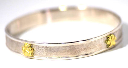 The gold and silver paw print bangle is hand crafted in sterling silver and 18 k yellow gold.  The bangle fits an average 7 inch wrist.  The width of the bracelet is 10 mm. x 2 mm.  and has a raised polished 2 mm. edge and a brushed recessed center section.  There are four 9 mm. x 7 mm. 18 k yellow gold two dimensional paws on it.  The bracelet weighs 31.3 grams and is solid.  A portion of the profits will be donated to the Animal Refuge League locate in Westbrook, Maine.