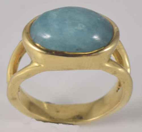 The oval paraiba gold tourmaline ring is hand crafted in Portland, Maine. The stone is a 15 mm. x 10 mm. oval horizontal set paraiba tourmaline cabochon ring. The stone is set in an 18 k yellow gold split shank ring. The ring is a size 7.25 and weighs 10.5 grams.